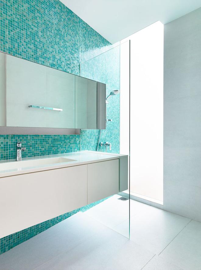 Một bức tường ốp gạch xanh nổi bần bật với mẫu phòng tắm