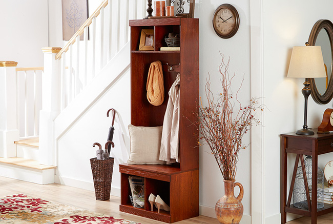 Cạnh góc cầu thang là chiếc giá treo quần áo làm từ gỗ có ngăn trên cùng đựng khung ảnh