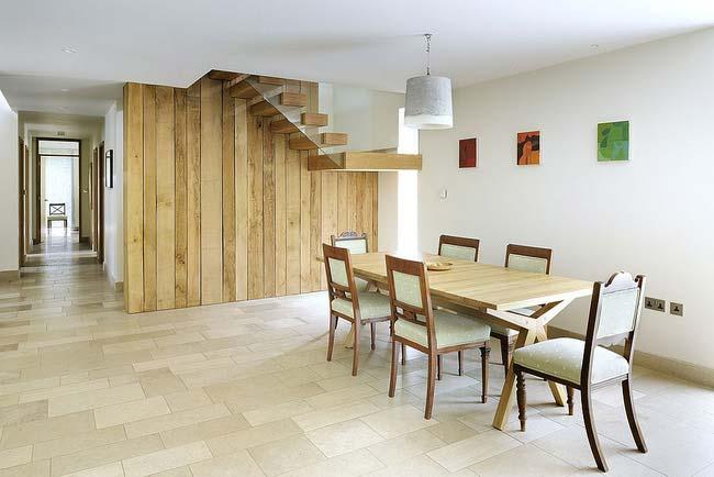 Bạn có thấy bức tường và cầu thang bằng gỗ tái chế dẫn dắt ánh nhìn của bạn một cách mãnh liệt trong thiết kế nhà ăn này không